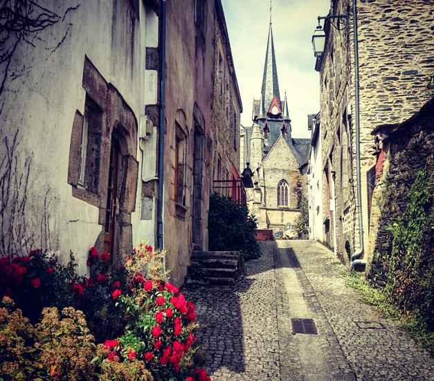 Serent town in Brittany, houses and church, flagstone road